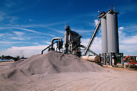 Stone and asphalt plant with pile of stone used in road repair and paving.