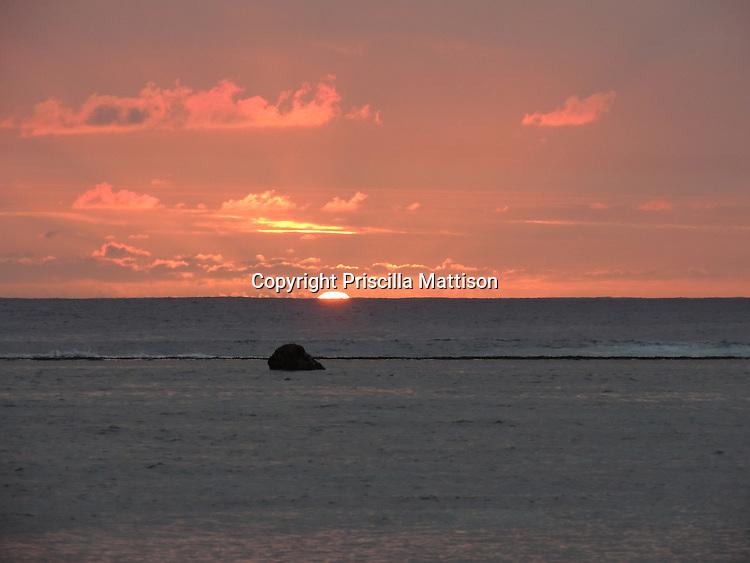 Rarotonga, Cook Islands - September 20, 2012:  The sinking sun lights up clouds over the lagoon.