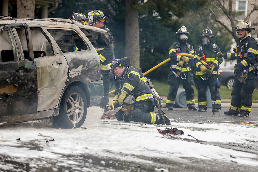 MANASQUAN, NJ — April 1, 2016 —Sean Price and other Manasquan firefighters use foam to battle a stubborn car fire on Broad Street at about 9:40am Friday morning. photo by Andrew Mills