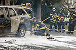MANASQUAN, NJ — April 1, 2016 — Sean Price and other Manasquan firefighters use foam to battle a stubborn car fire on Broad Street at about 9:40am Friday morning. photo by Andrew Mills