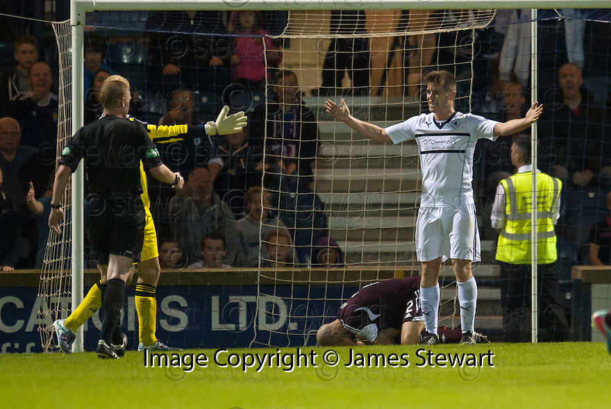 Raith Rovers' Dougie Hill protests his innocence as Hearts' Jamie Hamill goes down holding his face.