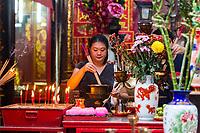 Sin Sze Si Ya Taoist Temple, Chinatown, Kuala Lumpur, Malaysia.  Woman Lighting Joss Sticks. Oldest Taoist temple in Kuala Lumpur (1864).