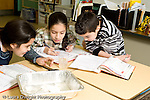 Education Elementary Public school grade 4 class with science specialist two girls and a boy working together on experiment small group horizontal