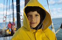DEUTSCHLAND, Ahrenshoop, Junge im Ostfriesennerz auf einem Zesenboot auf Darsser Bodden / GERMANY, child on sailing boat