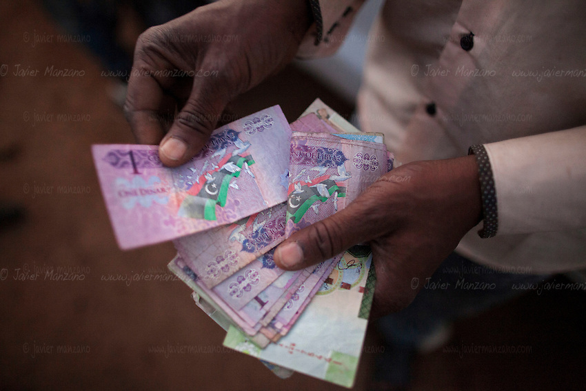 AGADEZ, NIGER — <br /> A smuggler counts the cash he needs to pay off the Libyan border guards for each migrant he transports into the country. Twenty U.S. dollars is the price charged per migrant entering the country.