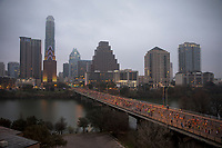 Fog covers the Austin skyline on a moody day in February as thousands of Austin Marathon runners take over Congress Avenue Bridge after the start of the race in downtown Austin, Texas.<br /> <br /> The Austin Marathon is an annual marathon held in Austin, Texas. It was founded in 1991 by Freescale Semiconductor, who served as title sponsor for fifteen years. The Austin Marathon annually hosts runners from all 50 states and more than 20 countries around the world. It is, as is Austin, the most popular Marathon in the World.