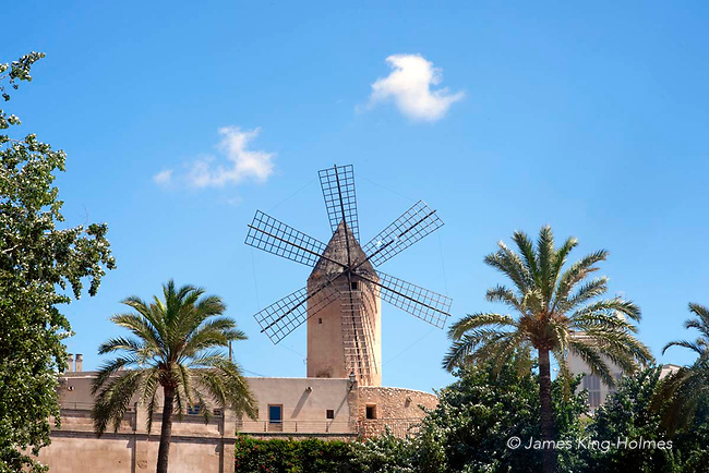 Windmills, Palma de Mallorca. Windmills dominate the high terrain of El Jonquet above the marina area in Palma de Mallorca, Balearic Islands, Spain above the many palm trees lining the Passeig Maritimo which runs along the waterfront