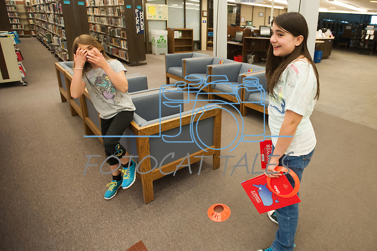 Katie Tubiello, right, and Sandra Tubiello look for course ideas during the Mini Golf Night at the Carson City Library on Friday, May 9, 2014. Kids and parents built a custom mini golf course throughout the library using anything at their disposal and engineering ideas to make a difficult course. Everything from tables to shelves were used to create creative courses.<br /> (Photo by Kevin Clifford/Nevada Photo Source)
