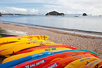 Kayaks on Beach, Paihia Bay, looking toward Waitangi Treaty Grounds in distance.  Tourist helicopter and cruise ship in background.  Paihia, north island, New Zealand.