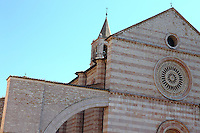 Assisi:  A part of the façade of the ancient church of Santa Chiara, with its beautiful alternance of white and rose-coloured bricks. The characteristic half-arcs are visible on the left.