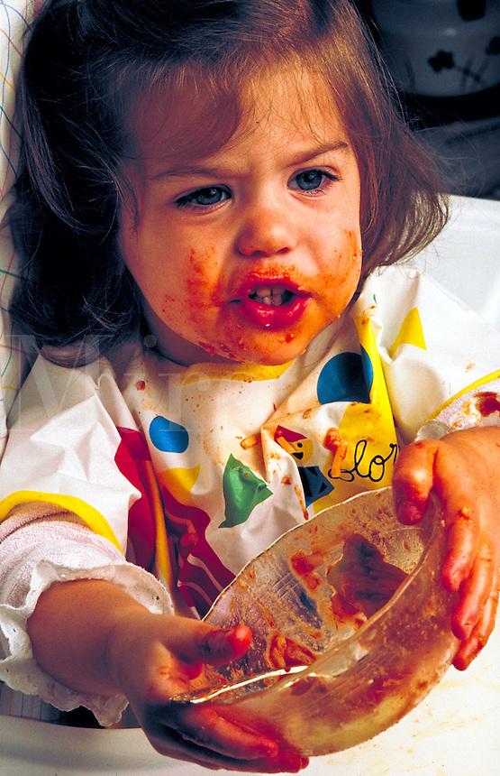 Toddler making a mess while eating pasta.