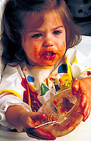 Toddler making a mess while eating pasta.
