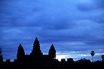 Angkor Wat Sunrise 01 - Angkor Wat temple silhouetted against a dark blue cloudy sky at dawn, from the causeway, Cambodia.