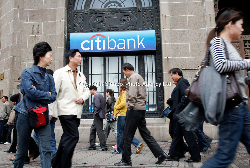 Pedestrians walk past a Citibank branch in Shanghai, China. A group of investors led by Citigroup agreed Thursday to pay $3.1 billion (euro 2.4 billion) to acquire a controlling stake in the Guangdong Development Bank, the first time a foreign-led consortium has won the right to manage a major Chinese bank..