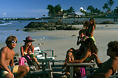 Ilheus, Bahia State, Brazil.  People on the beach sitting on chairs and people swimming in the sea in the background.