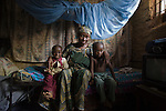 Mother and children with mosquito net in Kano, Nigeria.  Sleeping under a long lasting insecticide treated net every night prevents malaria.  Malaria, which is transmitted through the bite of an infected mosquito, is a major killer of children under five and pregnant women in Nigeria and the developing world.