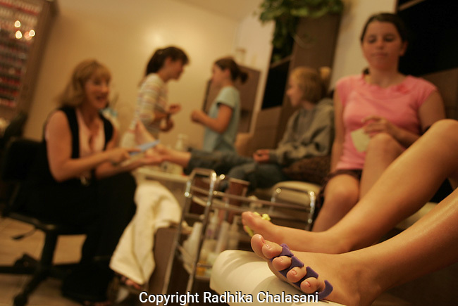 STUDIO CITY, CA-JUNE 10: A group of girls get pedicures during a party at the Belle Visage Day Spa June 10, 2004 in Studio City. The spa hosts parties for 9-18 year-olds which cost between 87-119 USD per person. Cake, lunch and limo services are additional. With teens and pre-teens (tweens) spending more and more money on health and beauty products a growing number of American spas are providing services to young people. (Photo by Radhika Chalasani)