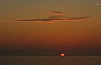Sun rises into a golden sky at beach