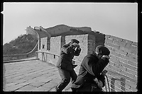 Chinese visitors dressed in Mao suits try to prevent their caps from being blown away by strong winds on the Great Wall near Beijing, China, 1985.