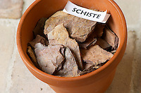 Plant pot with soil sample to illustrate different soil types, part of a series: schist schiste Chateau Villerambert-Julien near Caunes-Minervois. Minervois. Languedoc. Terroir soil. France. Europe. Schist slate soil.