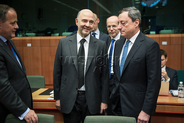 Pierre Moscovici , EU commissioner for Economic and financial affairs, taxation and customs union and Mario Draghi, President of the European Central Bank (R) at the start of a Eurogroup with European Finance Ministers meeting at EU council headquarters in Brussels, Belgium on 26.01.2015 The Eurogroup's meeting focus on Greece, after  leftist anti-bailout party SYRIZA won parliamentary elections by Wiktor Dabkowski