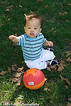 12 month old toddler boy outside sitting on grass language development pointing and saying word vertical