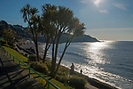 Swansea, UK, 26th March 2020.<br />A man walks his dog on the beach at Langland Bay near Swansea this morning as an early morning jogger runs past on a stunning spring morning.