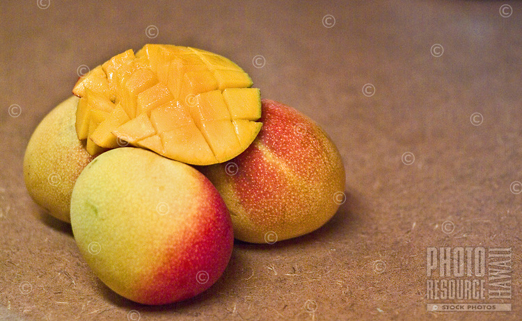 Four ripe mangos, with one cut open ready to eat