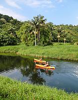 Two kayakers paddle the calm waters of Hanalei River, Kaua'i.