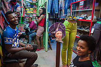 Nigeria. Enugu State. Enugu. Ogbete Main Market is the biggest commodity market. Two different shops, one selling fashion clothes (R) and the other (L)  traditional loin clothes. A man and four women, all Igbo, are laughing and talking together. Some work in the shops, the other are just visitors. Two manikins wears a head tie which is a women's cloth head scarf. The head tie is used as an ornamental head covering or fashion accessory, or for functionality in different settings. Its use or meaning can vary depending on the country and/or religion of those who wear it. The head tie is called gele in Nigeria. Ogbete main market is the choice market for wholesale buyers and sellers. It is segmented into lines and lock-up shops. Each line is made up of various lock-up shops occupied by traders dealing on similar or related goods. In Ogbete, some of the lines are numbered alphabetically such as K-line, M-line D-line etc. However, some other major lines are not numbered alphabetically, they are railway line or electronics line, provision line, plastic line, cosmetic line, books line etc. Residents of Enugu usually prefer going to Ogbete for major shopping, to buy things in bulk, to purchase quality and original goods, to have access to varieties, to buy new products and to buy goods at wholesale or company price. Apart from clothing and textile materials, prices of commodities in the market are moderately cheap. Enugu is the capital of Enugu State, located in southeastern Nigeria. 1.07.19 © 2019 Didier Ruef