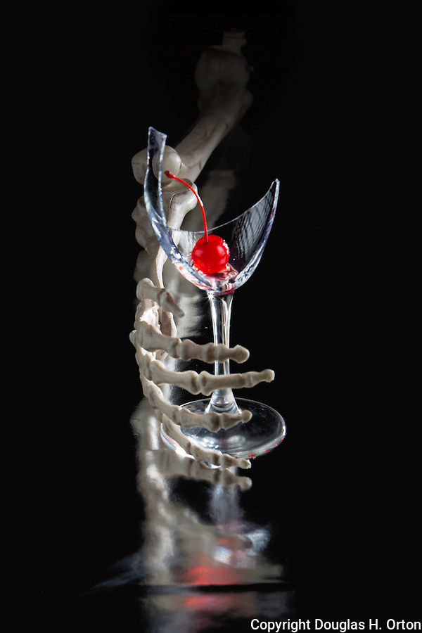 Skeletal hand holding a broken wine glass on black background with cherry and reflections.  Signifying addiction. Photographed in-studio on reflective mat.