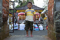 Bali, Indonesia.  Little Hindu Balinese Boy at Entrance to the Temple.  Pura Dalem Temple, Dlod Blungbang Village.