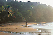 Osa Peninsula, Costa Rica. Tourist paddling along the waters edge on the beach at Marenco.