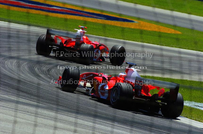 Michael Schumacher (#1-Ferrari) leads teammate Rubens Barrichello (#2-Ferrari)