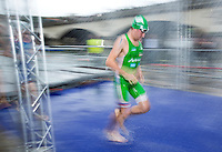 07 JUL 2012 - PARIS, FRA - David MacNamee (E.C.Sartrouville Triathlon) runs through the showers after the swim during the elite men's French Grand Prix round during the 2012 Triathlon de Paris at the Pont d'Lena, Paris, France (PHOTO (C) 2012 NIGEL FARROW)
