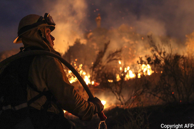 A fireman works to contain the 6,000 acre Border Fire in eastern San Diego County, California, USA, on Tuesday, June 21, 2016.