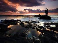 Two young girls in silhouette watch a brilliant and colorful sunset from Kohanaiki, Kailua-Kona, Big Island.