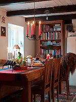 A Swedish wrought iron chandelier hangs above a festive spread laid out on the homemade kitchen table