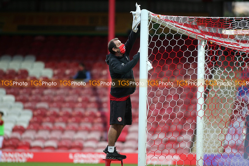 A member of the Brentford ground staff wipes the post and crossbar in the drinks break during Brentford vs Barnsley, Sky Bet EFL Championship Football at Griffin Park on 22nd July 2020