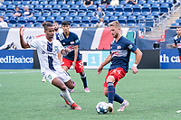 FOXBOROUGH, MA - JULY 4: Pierre Cacet #44 of the New England Revolution II passes the ball as Andrew Booth #19 of Greenville Triumph SC pressures during a game between Greenville Triumph SC and New England Revolution II at Gillette Stadium on July 4, 2021 in Foxborough, Massachusetts.