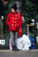 Saturday 14 December 2013<br /> Pictured:A lady Stands with her many bags amongst the  in front of a Chrostmas display at  Swansea's busy Oxford Street in the City Centrre<br /> Re: Towns and City's are busy with shoppers  across the UK as Christmas  is only 10 days away.