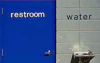 "AJ1717, restroom, water fountain, Blue door of a restroom next to a water fountain hanging on a gray wall. The words (""""restroom, water"""") are on the (door, wall)."