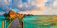 Panorama on overwater bungalows in the turquoise lagoon, with golden sunset light, in Tikehau Tuamotus, French Polynesia, South Pacific Ocean