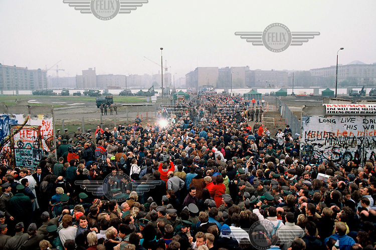 Thousands of East Germans stream through the Berlin Wall a few days after its opening on November 9th, 1989 when the East German Government announced it would start granting exit visas to anyone who wanted to go to the West. The announcement was misinterpreted as meaning the border was now open and East German border guards were unable to stop the rush of people to the Wall. Within hours people were smashing sections of the Wall with their own hand tools and these first cracks led to the complete opening of the border within days.