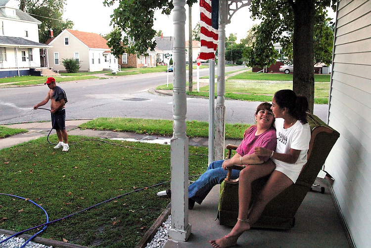 """""""This is the American dream and we are living it,"""" said Marisela Chavez, enjoying a quiet summer evening with Stephanie, 11, one of her three daughters. Chavez came to Beardstown in 1995; she works for the school system's bilingual program and her husband Valentine, left, works at Excel. Like many Mexican families in Beardstown, they purchased a home next to Caucasian neighbors and adopted local customs, such as flying the flag and maintaining their lawn...Kristen Schmid Schurter/SJ-R"""