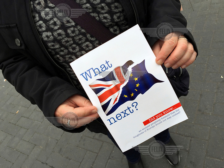 A woman holds a leaflet that reads: 'What Next?' (in reference to Brexit) distributed by a religious group.