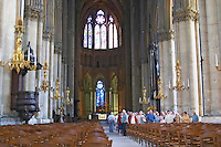 Inside the cathedral in Reims with impressive stained glass windows, chandeliers, chairs and a group of people standing backwards facing the back end of the cathedral all looking up. the middle window is by Chagall, Reims, Champagne, Marne, Ardennes, France, low light grainy grain