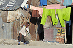 A girl sweeps the ground in front of her meager home in Cite Soleil, a sprawling poor portion of Port-au-Prince, Haiti.