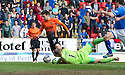 Dundee Utd's Ryan Dow goes down in the box under a challenge from St Johnstone keeper Alan Mannus but referee John Beaton plays on.