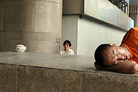 CHINA. Beijing. Man sleeping outide of Beijing West Train Station. 2007.